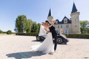 jeunes mariés s'embrassant devant une vieille voiture garée devant le château Agassac à Ludon-Médoc en Gironde sous l'oeil du photographe de mariage à Bordeaux Sébastien Huruguen