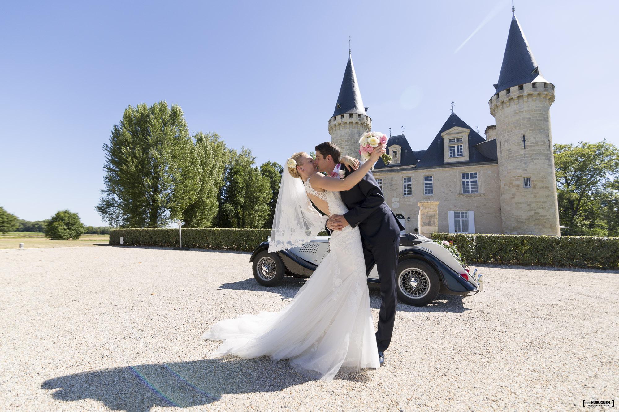 Sebastien et Maryia s'embrassent devant le chateau d'Agassac à Ludon Médoc près de Bordeaux, belle robe de mariée