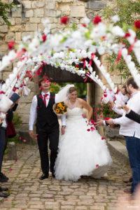 Les mariés sont accueillis par une haie d'honneur de couronnes de fleurs au chateau médiéval de Langoiran Sébastien Huruguen photographe de Mariage à Bordeaux