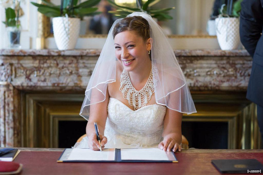 mariee-en-robe-blanche-et-voile-souriante-durant-la-signature-mairie-de-bordeaux-mariage-civil-sebastien-huruguen-photographe-professionnel