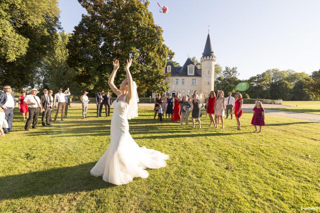 la jolie mariée dans sa belle robe blanche de noce lance son bouquet de mariage aux demoiselles sur la pelouse du parc du Chateau Agassac à Ludon-Médoc