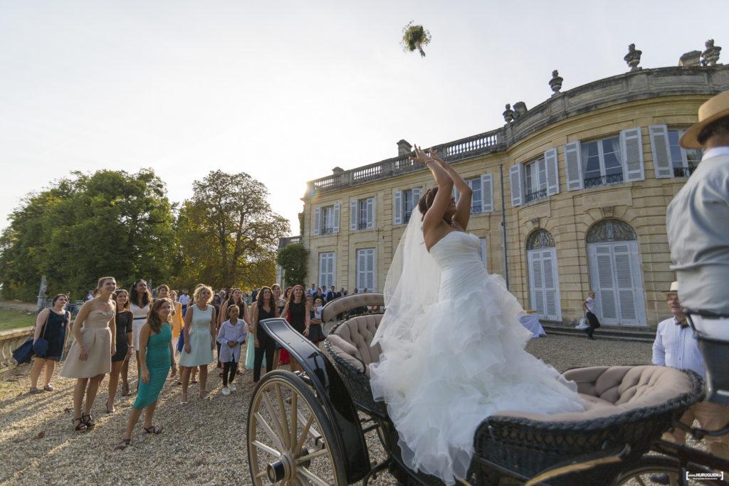 Dans le parc du Chateau de la Dame Blanche au Taillan Medoc, la jolie mariée dans sa belle robe blanche lance son bouquet de mariage aux demoiselles depuis la calèche qui l'a conduite au lieu de la réception et du vin d'honneur du mariage