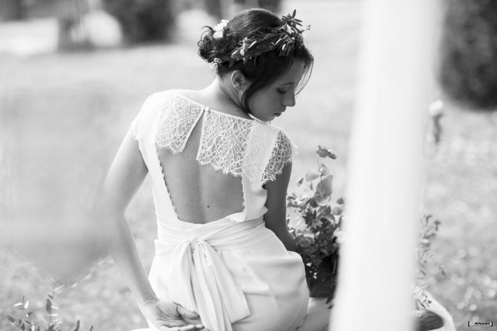 superbe robe de mariage dos nu portée par la mariée dans le jardinb du parc du chateau bomale à libourne dans les environs de Bordeaux en nouvelle aquitaine photographié par le photographe de mariage bordelais Sébastien Huruguen couronne de fleurs dans les cheveux et bouquet de fleurs dans les mains