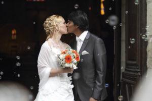 couple de jeunes mariés qui s'embrassent à la sortie de l'église en Gironde sous l'oeil du photographe de mariage à Bordeaux Sébastien Huruguen