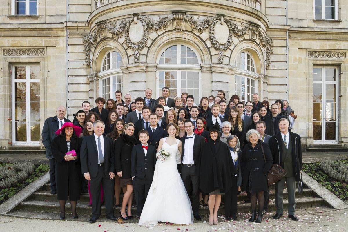 Photo de groupe de mariage famille et invités autour du couple de jeunes mariés à la mairie de Talence dans le parc Peixoto par le photographe de mariage à bordeaux Sebastien Huruguen
