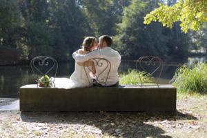 couple de mariés qui s'embrassent sur un banc du parc Majolan à Blanquefort lors de leur séance photo de couple Trash The Dress Day After en Gironde sous l'oeil du photographe de mariage à Bordeaux Sébastien Huruguen