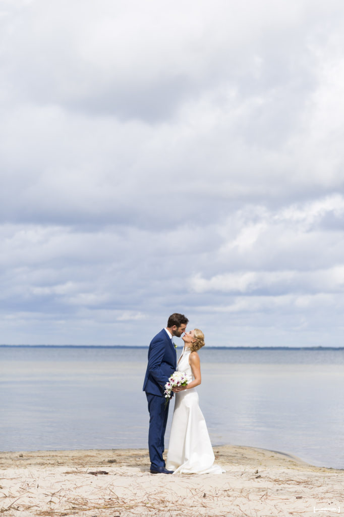 un joli couple de jeunes mariés qui s'embrassent sur la plage au bord de l'eau, photo de mariage au lac de Carcans Maubuisson