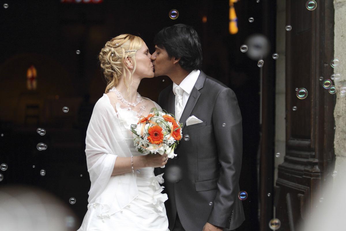 couple de jeunes maries indien et francaise qui s'embrassent à la sortie de l'église sous les bulles et les applaudissements des témoins et de la famille