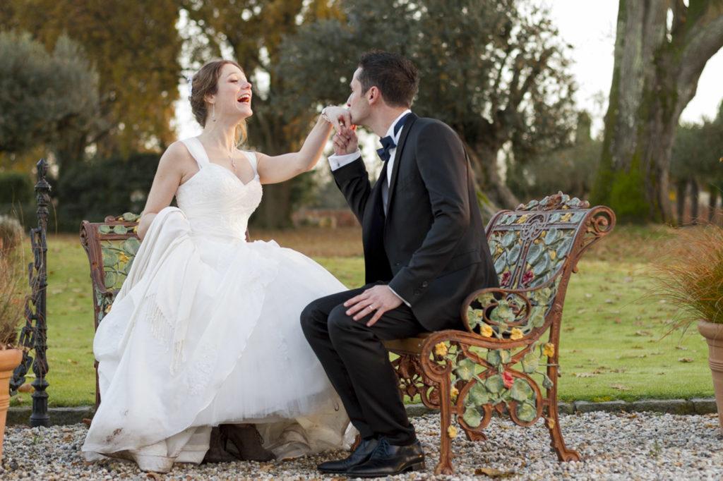 couple de jeunes mariés souriants dans les jardins du domaine du chateau Pape-Clément à Pessac en Gironde sous l'oeil du photographe de mariage à Bordeaux Sébastien Huruguen