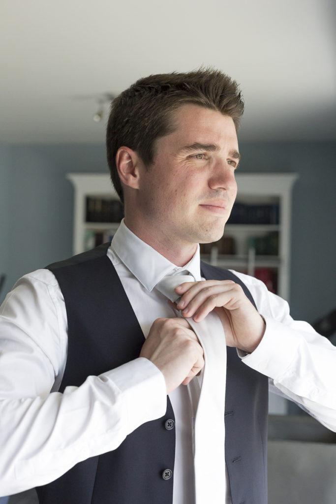 Le futur mari se prépare pour sa journée de mariage et s'habille avec une jolie cravate pour son scostume Photographe mariage Bordeaux Sebastien Huruguen