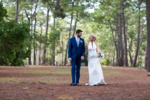 couple de jeunes mariés marchant main dans la main dans le sous bois de la forêt médocaine au bord du lac de carcans maubuisson en Gironde sous l'oeil du photographe de mariage à Bordeaux Sébastien Huruguen
