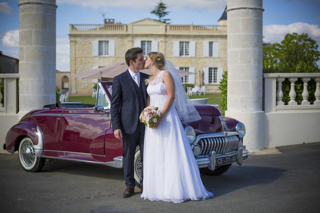 Photographe Mariage Bordeaux Sebastien Huruguen chateau lafitte laguens yvrac couple de maries qui s'embrassent devant entree du chateau et vieille voiture peugeot