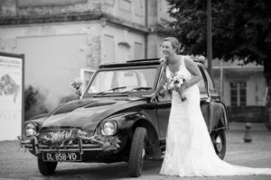 magnifique mariée posant en robe blanche bouquet de fleurs à la maison devant la citroen dyane qui l'a amené a la cérémonie de son mariage au bord des vignes de la rive droite en Gironde sous l'oeil du photographe de mariage à Bordeaux Sébastien Huruguen