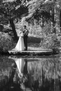 couple de jeune mariés au bord d'un plan d'eau en noir et blanc avec un joli reflet
