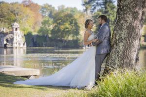 couple de jeunes mariés adossés à un arbre du parc majolan à Blanquefort superbe robe blanche de mariée avec une longue traine en Gironde sous l'oeil du photographe de mariage à Bordeaux Sébastien Huruguen