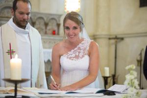 la mariee signe sur l'autel a l'église d'Yvrac a cote du pretre ceremonie de mariage religieux catholique bordeaux sebastien huruguen jolie robe de mariage