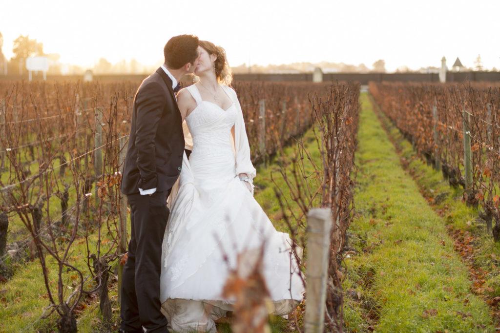 couple de jeunes mariés s'embrassant au coucher de soleil dans les vignes du chateau Pape-Clément à Pessac en Gironde sous l'oeil du photographe de mariage à Bordeaux Sébastien Huruguen