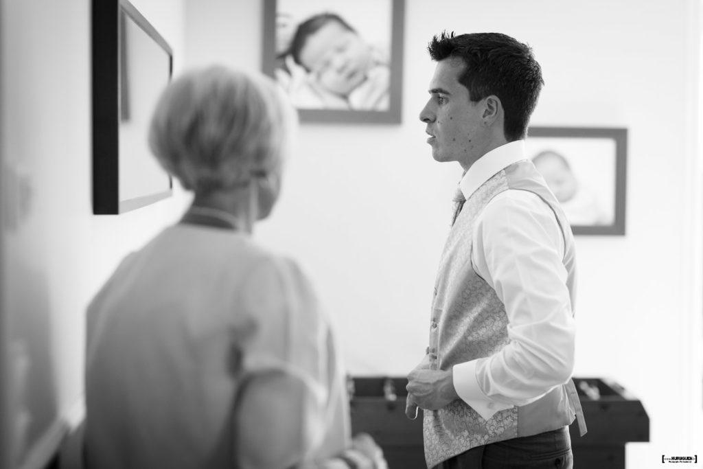 Le futur mari se prépare devant le miroir avec l'aide de sa mère habillage photographe mariage bordeaux Sébastien Huruguen