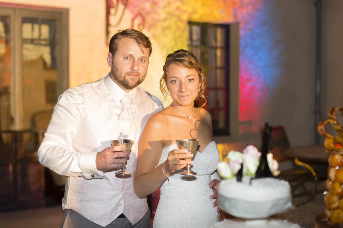 Couple de jeunes mariés qui trinquent lors de la présentation du dessert au repas de mariage après avoir couper le gateau, présentation du gateau en extérieur, robe de mariée, sebastien huruguen photographe mariage bordeaux