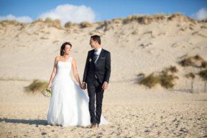 Couple de mariés marchant main dans la main sur le sable de la plage de Carcans Maubuisson dans le Médoc en Gironde sous l'oeil du photographe de mariage à Bordeaux Sébastien Huruguen