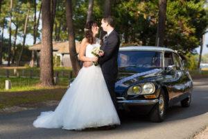 jeunes mariés dans la lumière devant la voiture de leur mariage en Gironde sous l'oeil du photographe de mariage à Bordeaux Sébastien Huruguen