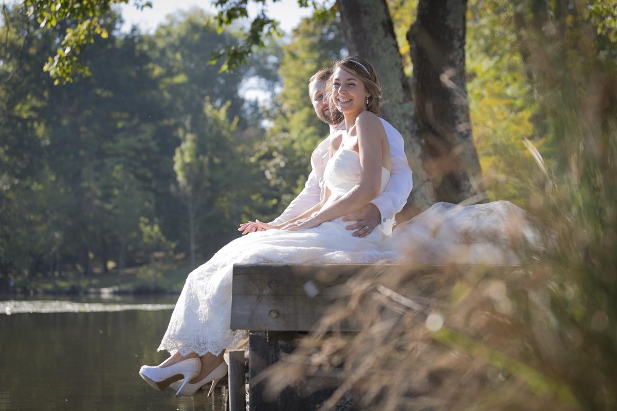 Jolie mariée et son mari en train de sourire assis au bord d'un plan d'eau du parc de majolan à Blanquefort avec de jolis escarpins à hauts talons blancs avec plateforme photographe mariage bordeaux sebastien huruguen