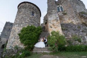 couple de jeunes mariés posant sur les marches du chateau médiéval de Langoiran