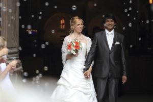 Mariés qui sortent de l'église sous les bulles et la joie franco indien sebastien huruguen photographe mariage bordeaux