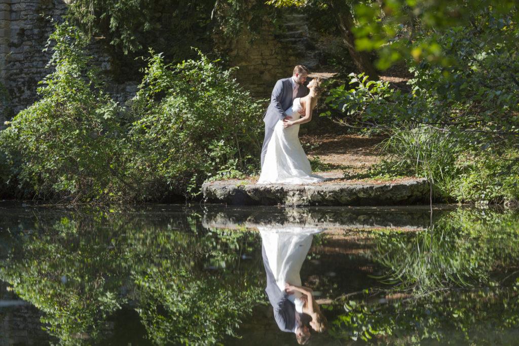 Couple de jeunes mariés posant au bord d'un lac avec un joli reflet dans l'eau, photo prise lors d'une seance trash the dress au parc de majolan a blanquefort dans la région bordelaise par le photographe de mariage sebastien huruguen à Bordeaux