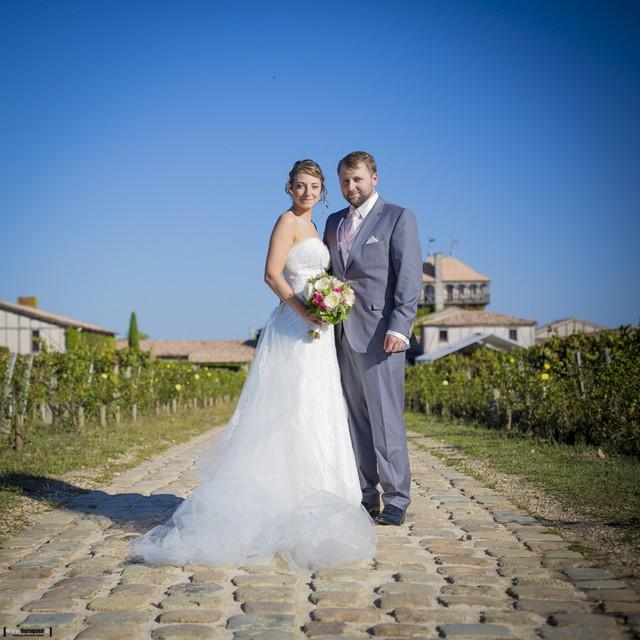 Couple de jeunes mariés en costume et robe de mariage blanche devant le Chateau Smith Haut Lafitte à Bordeaux par Sébastien Huruguen photographe Mariage