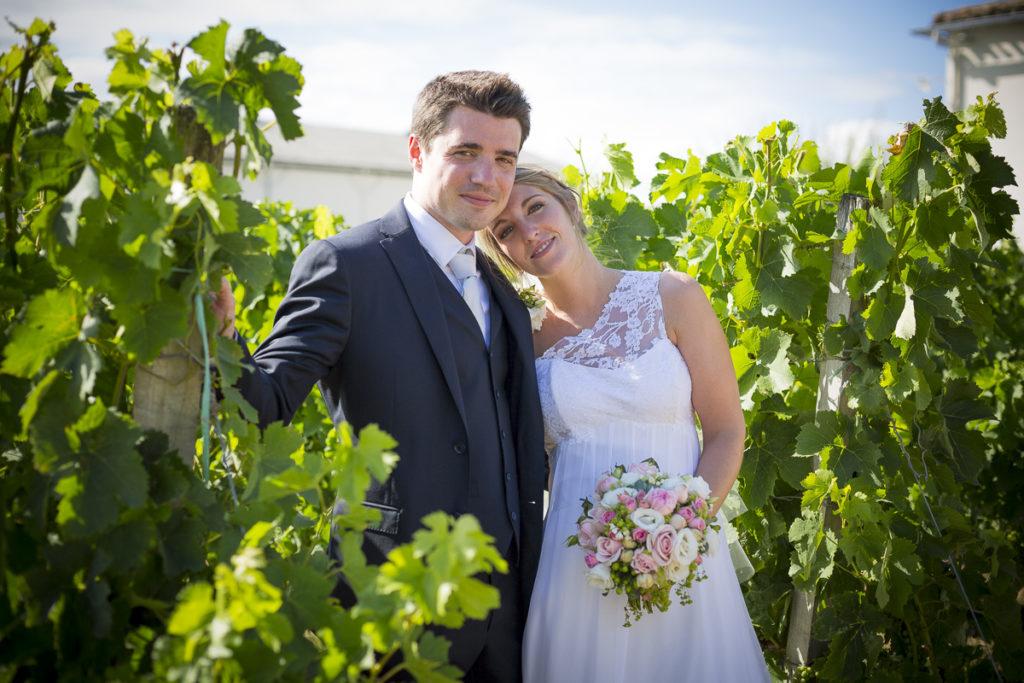 couple de jeunes mariés qui posent entre les vignes au soleil couchant dans les rangs de vignes du chateau Lafitte Laguens à Yvrac dans la région bordelaise, la mariée tient sont bouquet de mariage et pose sa tête sur l'épaule de son mari dans son joli costume bleu de mariage - sebastien huruguen