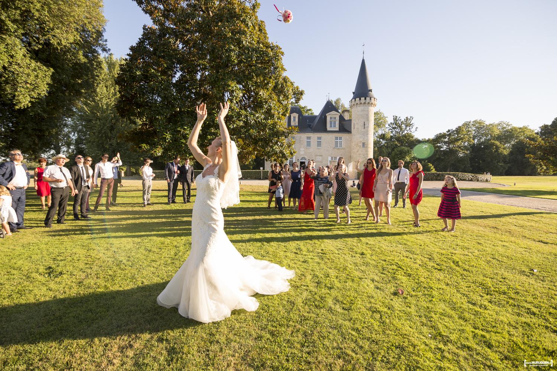 La mariée en belle robe blanche lance son bouquet de fleurs le jour de son mariage à Bordeaux dans le jardin du parc devant le chateau Agassac à Ludon-Médoc