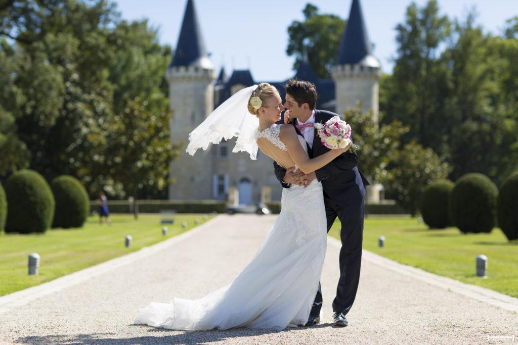 couple de jeunes mariés heureux qui s'embrassent devant le chateau d'Agassac à Ludon-Médoc dans la région de Bordeaux immortalisé par le photographe professionnel de mariage Sebastien Huruguen