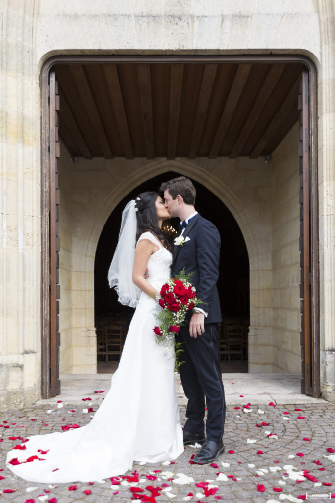 couple-mariés-baiser-sortie-eglise-macau-ceremonie-religieuse-mariage-fleurs-roses-rouge-sebastien-huruguen
