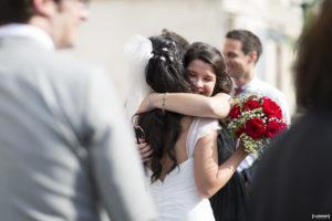 mariée serrée dans les bras de ses amies qui la félicitent pour son mariage