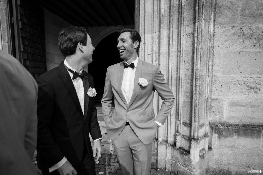 éclats de rires entre le marié et son témoin à la sortie de l'église