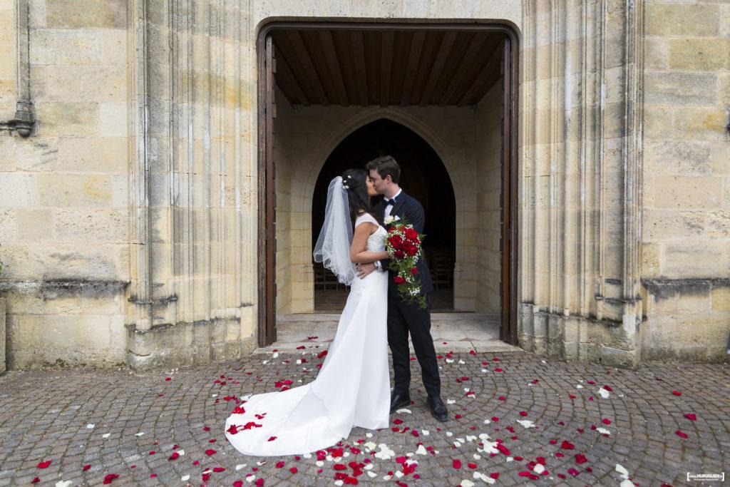 les-maries-sembrassent-a-la-sortie-de-leglise-sebastien-huruguen-photographe-mariage-bordeaux