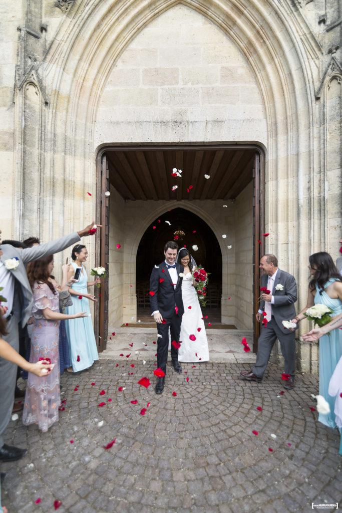Sortie des mariés sous les jets de pétéles de roses rouges et blanches