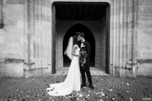 belle photo en noir et blanc où le couple de jeunes mariés s'embrassent à la sortie de la messe à Macau