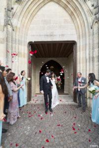 Sortie des mariés à l'église de Macau près de Bordeaux avec lancés de pétales de roses rouges et blanches Sébastien Huruguen photographe mariage Bordeaux