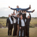 les témoins portent le jeune marié et le font sauter en l'air mariage château haut-bourcier blaye gironde sebastien huruguen photographe bordeaux